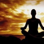 Female sillhouette in lotus position meditating against a colourful sunset
