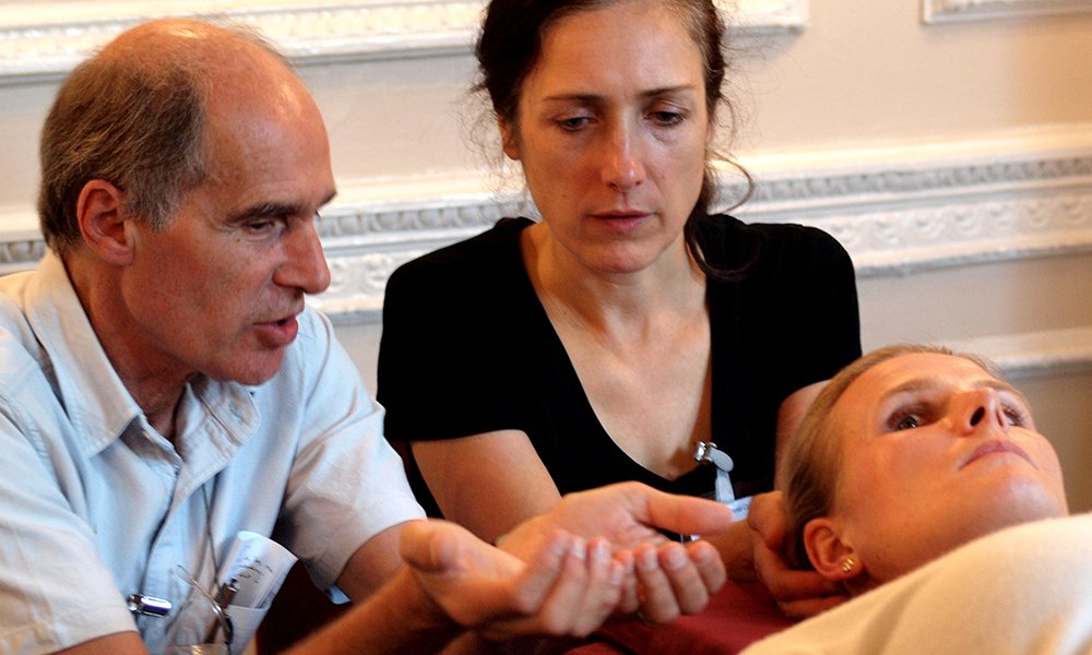 Tutor teaching osteopath demonstrating cupped hands
